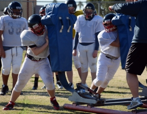 Players prepare for a game by hitting the blocking sled. (Photo by Mariana Rios)