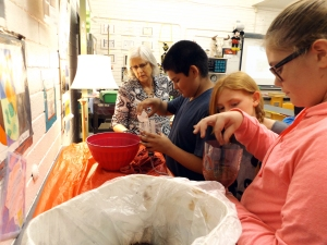 Students in Mrs. Gail McFarland's enrichment class make aquariums from soda bottles, soil, and seeds. The students' objective was to create a livable habitat for a goldfish. From left are seventh graders Frank Sanches, Maya Lindstrom, and Kendra Friederich. (Photo by SeAnna Brennan)