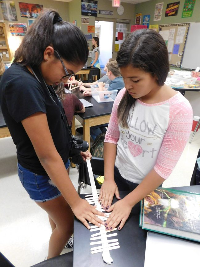 Isabella Vasquez, 7, and Emely Zepeda, 7, tape their bridge together. (Photo by Carissa LaFrance)