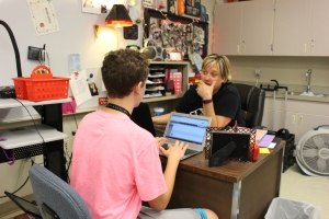 Teacher Regan Roach confers with a student updating his blog for the 20 percent project, which encouraged students to spend 20 percent of their class time working on a project they are passionate about. (Photo by Megan Ash)