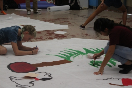 Finishing the final draft, Mya Palomino, 8, and Kaylee Smith, 8, paint a poster for the fall dance. (Photo by Hannah Molino)