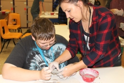 Mrs. Baumann helps James Cox, 7, shape a piece of his clay project. (Photo by Isabella Vasquez)